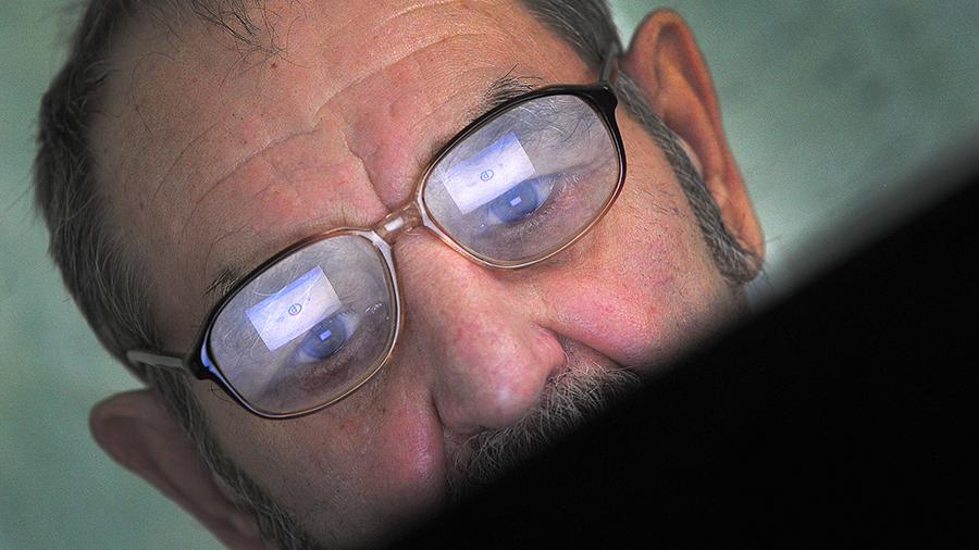 Пенсионер во время занятия в компьютерном консультационном центре для пожилых людей