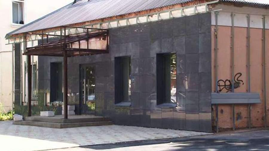 Фасад дореволюционного здания вОрле на улице Горького, 12 зашивают черными декоративными плитами.