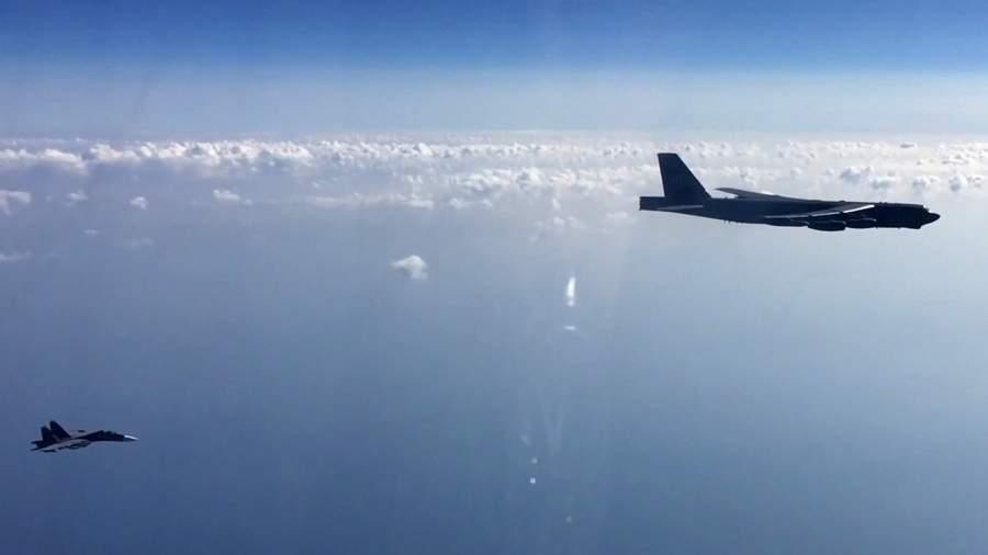 Russian Su-27 fighter and American strategic bomber Boeing B-52H Stratofortress in the sky over the Black Sea
