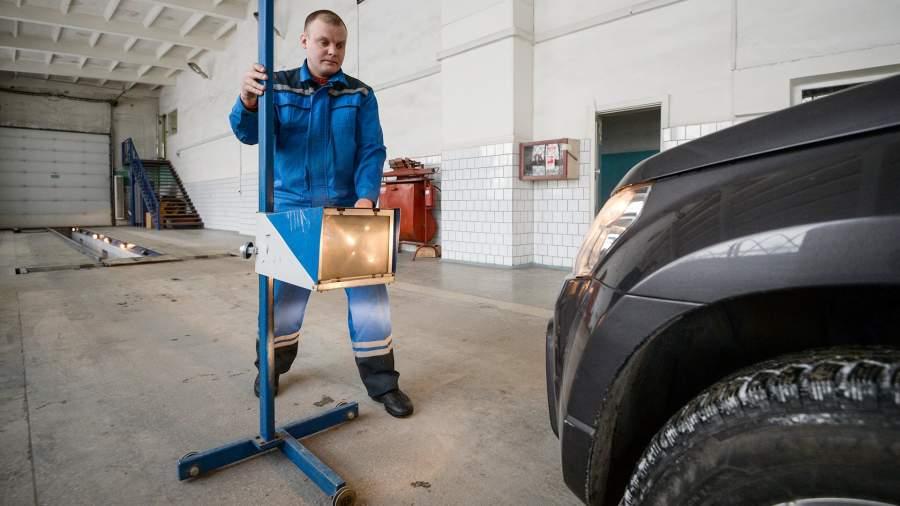Сотрудник станции ТО проводит технический осмотр автомобиля