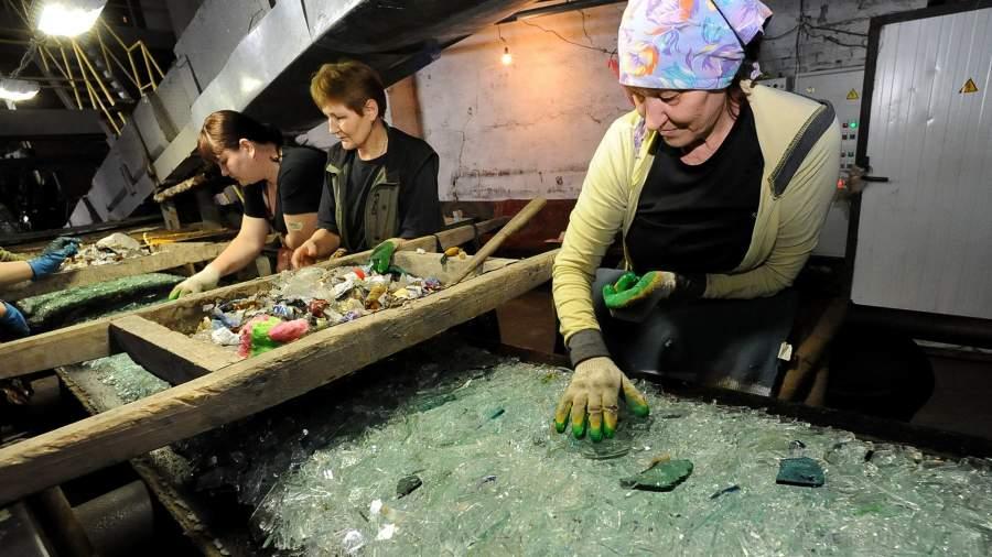 Рабочие очищают стеклобой от мусора на транспортерной линии
