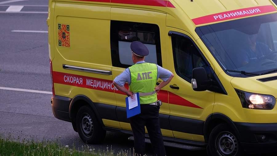 Сотрудник Дорожно-патрульной службы ГИБДД и автомобиль скорой медицинской помощи на дороге