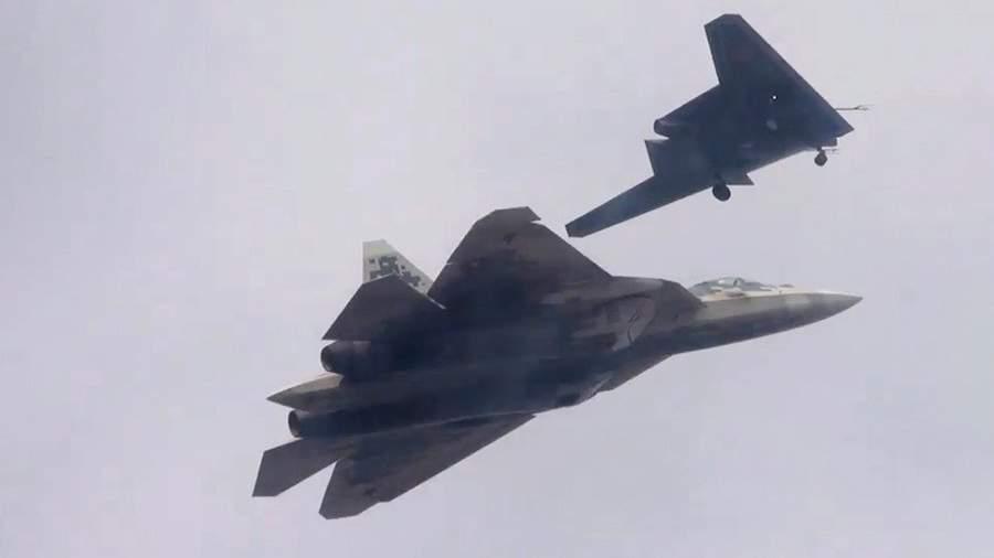 Новейший ударный беспилотник «Охотник» во время совместного полета с Су-57 на одном из испытательных аэродромов Минобороны России