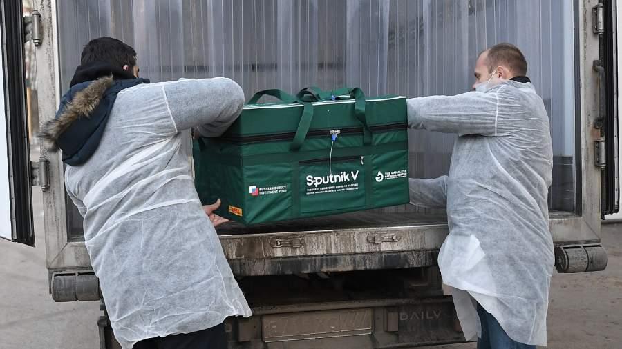 Сотрудники грузят контейнер с вакциной Sputnik V
