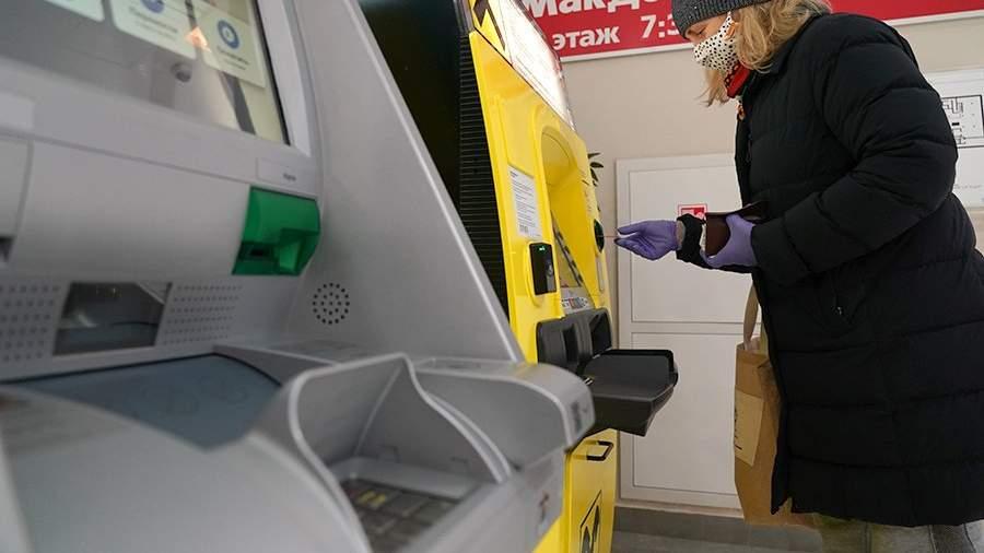 Женщина снимает деньги в банкомате