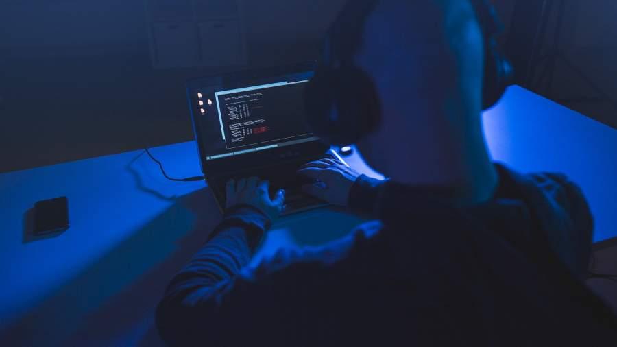 Хакер с ноутбуком в темной комнате