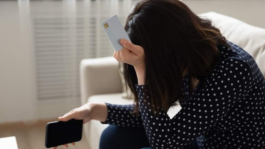 Расстроенная девушка с кредитной картой и телефоном