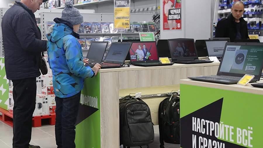 Покупатели и продавец-консультант в магазине электроники и бытовой техники