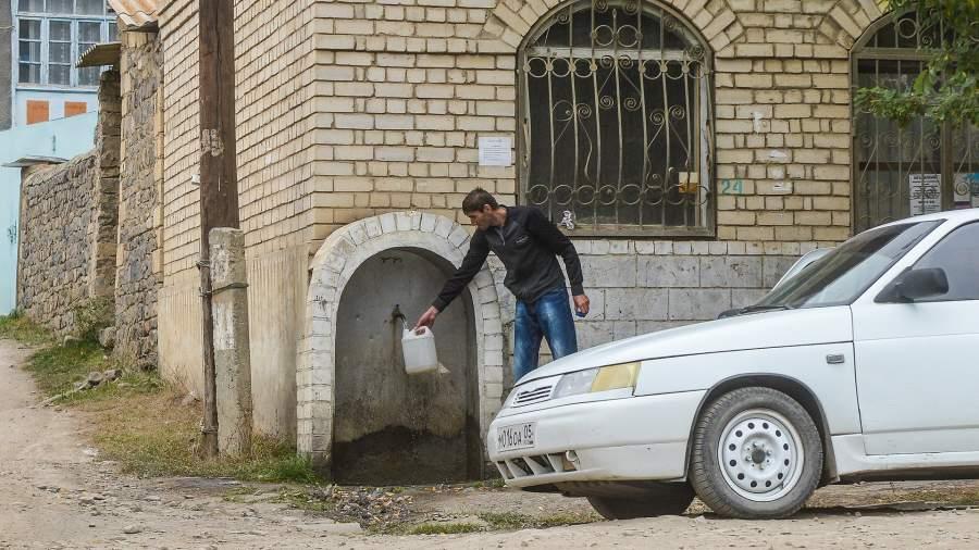 Мужчина набирает воду в канистру на улице дагестанского села