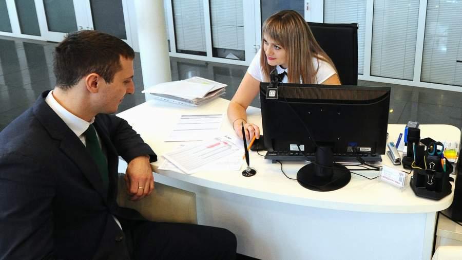 Сотрудница рассказывает клиенту об условиях получения кредита