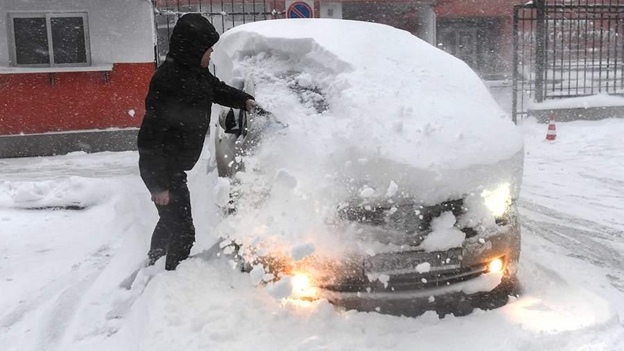 Мужчина расчищает автомобиль от снега во время снегопада в Симферополе