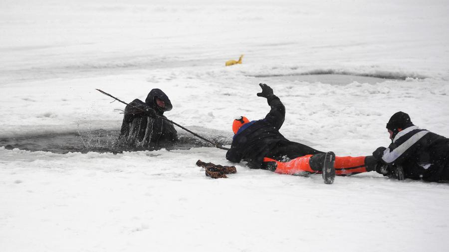 Сотрудники МЧС России вытаскивают из воды условно пострадавшего во время отработки действий по ликвидации условных чрезвычайных ситуаций на водных объектах зимой