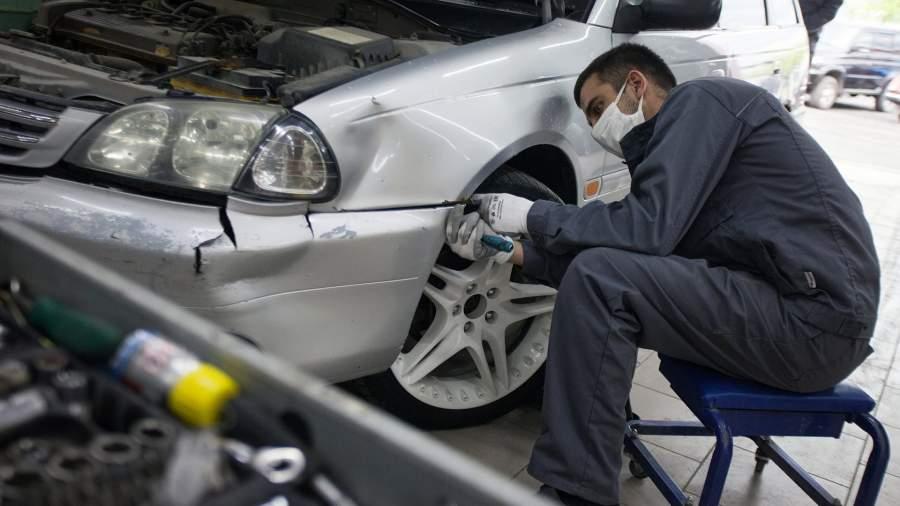 Сотрудник разбирает автомобиль перед дальнейшей покраской в центре кузовного ремонта