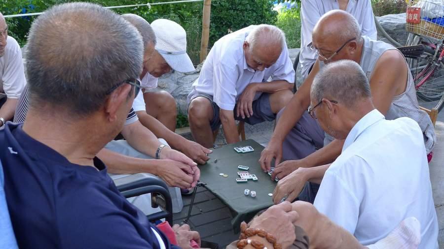Older Chinese people play dominoes