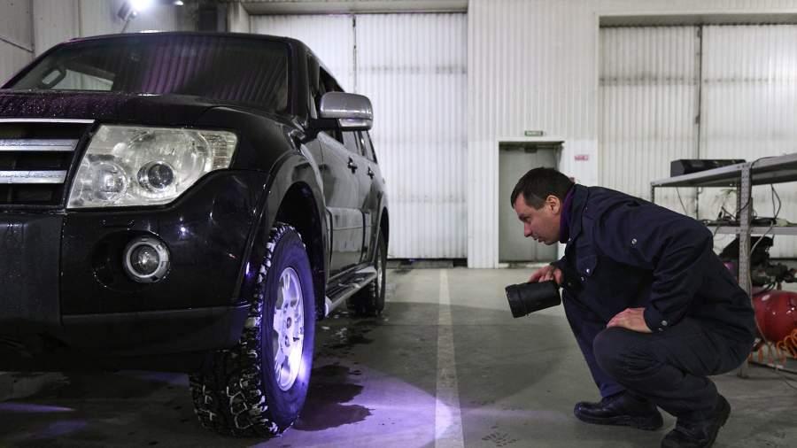 Технический эксперт проводит осмотр автомобиля