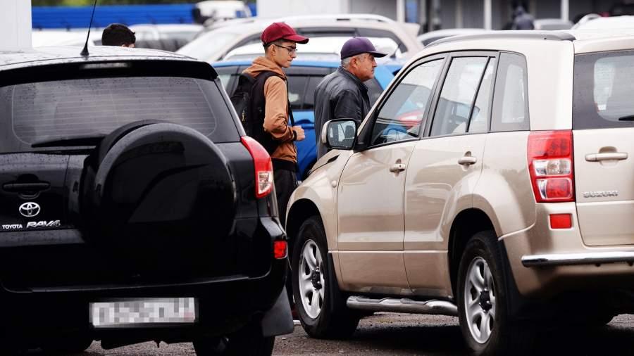 Люди осматривают подержанные автомобили, выставленные на продажу