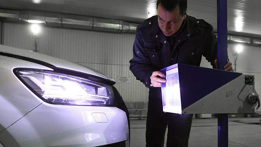 Технический эксперт проводит осмотр автомобиля на пункте технического осмотра