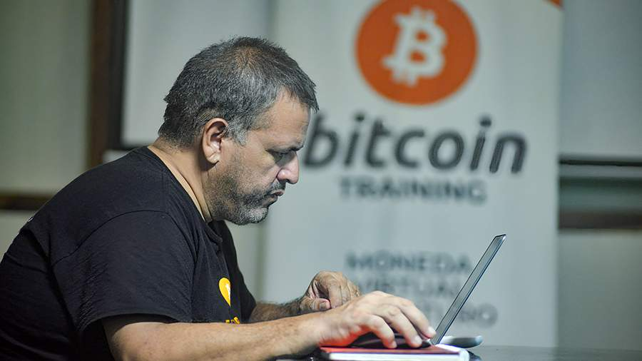 Человек за ноутбуком на фоне баннера с логотипом Биткоина