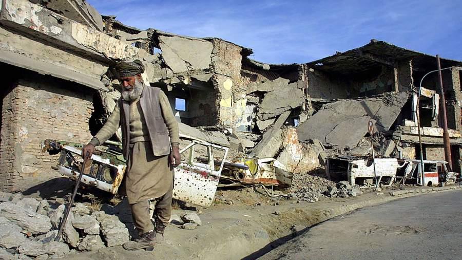 Житель Афганистана на фоне разрушенных домов