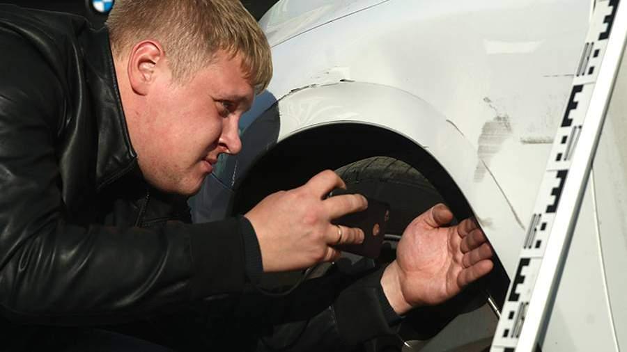Эксперт страховой компании во время осмотра поврежденного автомобиля