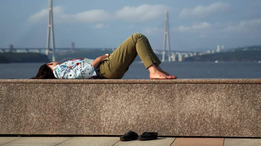 Девушка лежит на набережной Владивостока